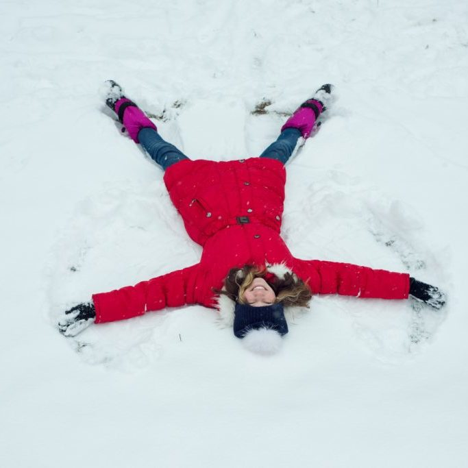 Winter time,cheerful girl having fun in the snow, top view.
